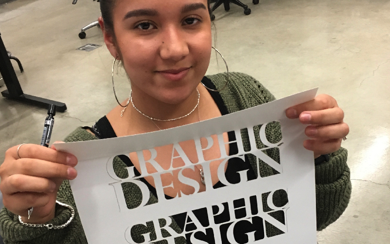 Design student holding laser cut artwork