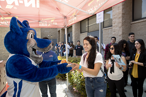 Photo of Cody the Coyote handing food to a student employee