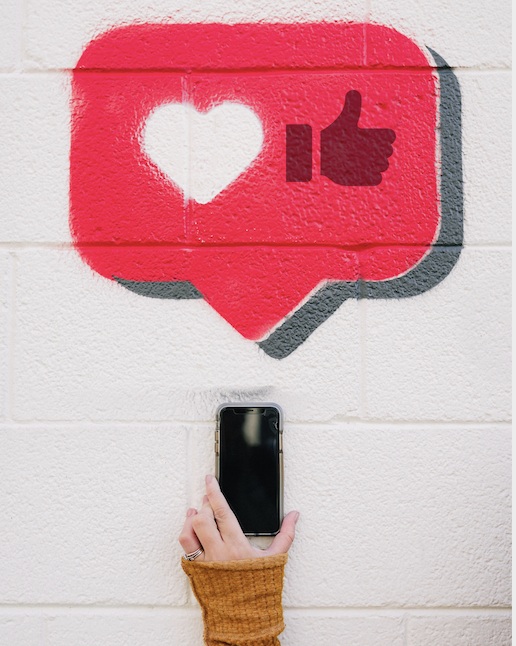 Woman holding up phone with picture of heart and like sign in the background