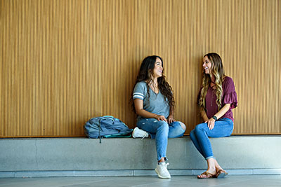 Students leaning against a wall talking
