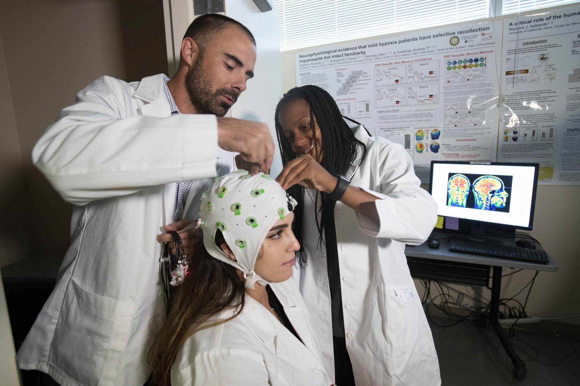 Richard Addante and Constance Greenwood make adjustments to an EEG device worn by Raechel Marino. The Addante and the students are developing a mobile EEG device that can be worn by astronauts to measure their brain activity.
