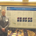Dr. Clapper in front of Poster