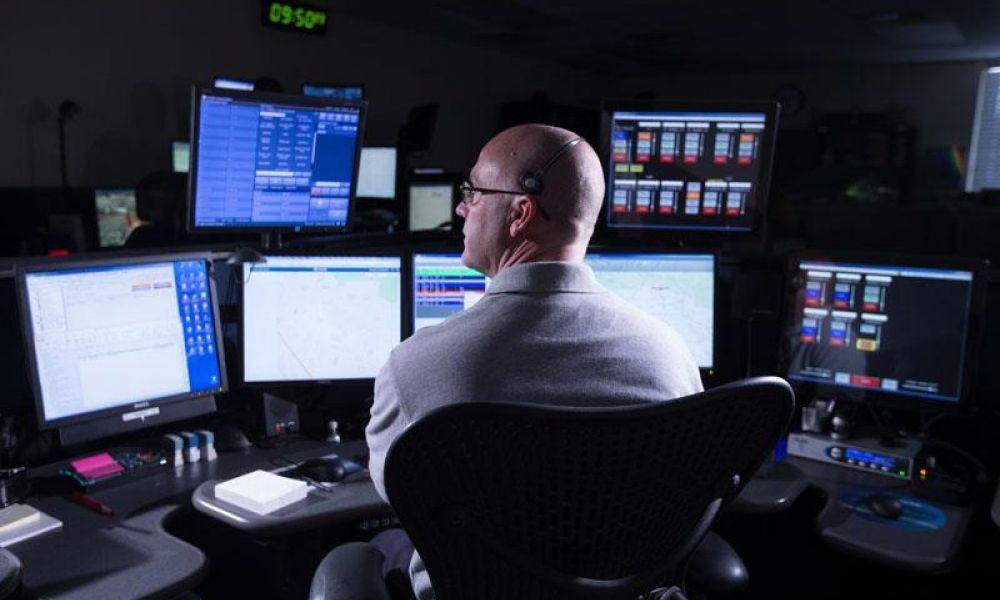 Man on computer with 7 monitors