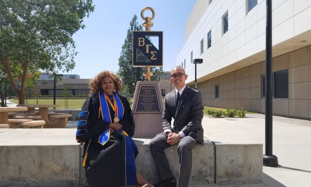 Dr. Beer & student in front of college BGS statue