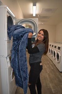 student at laundry mat taking blanket out of dryer