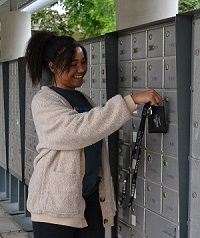 student opening up resident mailbox with key