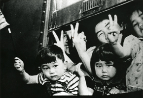 Japanese American children waving from train windows