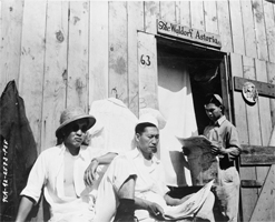 Photograph shows three interned Japanese men sitting by a wooden building
